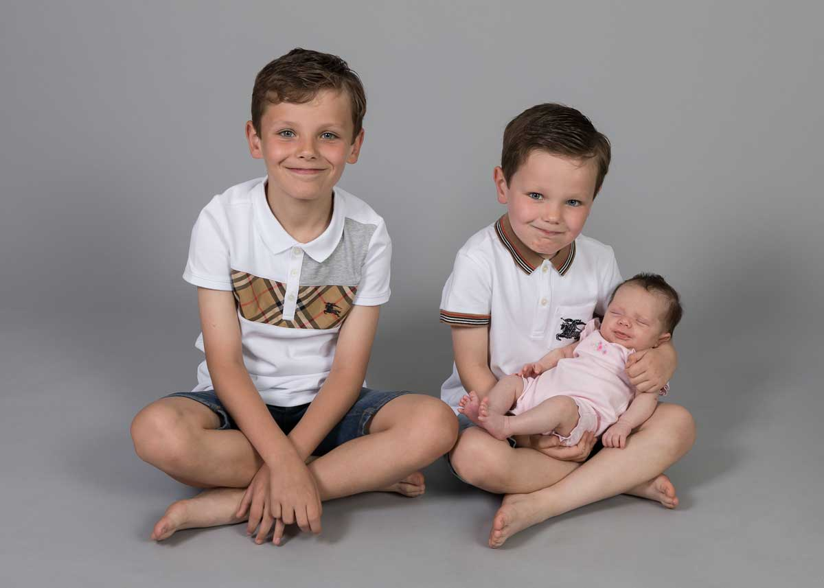 Brothers holding baby